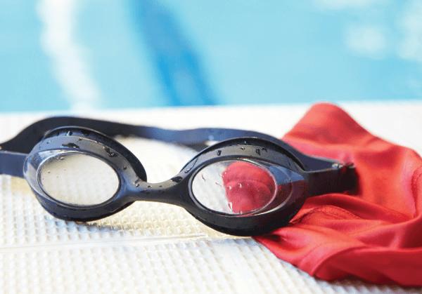 Plavecke okuliare na kraji bazena na cervenej kupacej ciapke